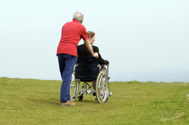 man pushing woman in wheelchair: Classic Vans Mobility & Wheelchair Vans article